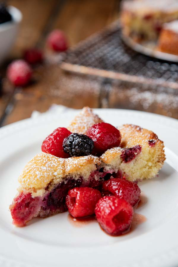 plate with a slice of butter cake and raspberry liqueur infused berries.