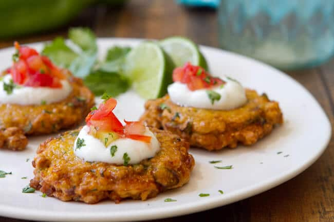 hatch chile and corn fritters on a plate garnished with sour cream and salsa.