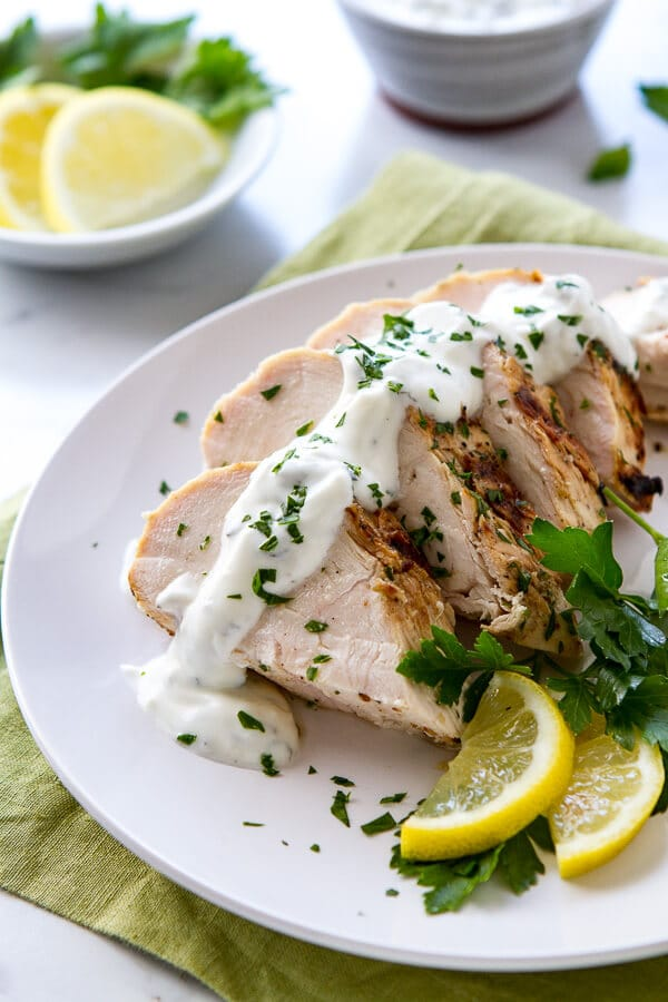 Yogurt, lemon and mint grilled chicken sliced on a plate.